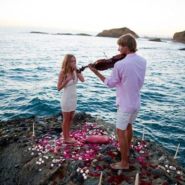 На берегу моря со скрипкой в руке и лепестками роз в ногах.