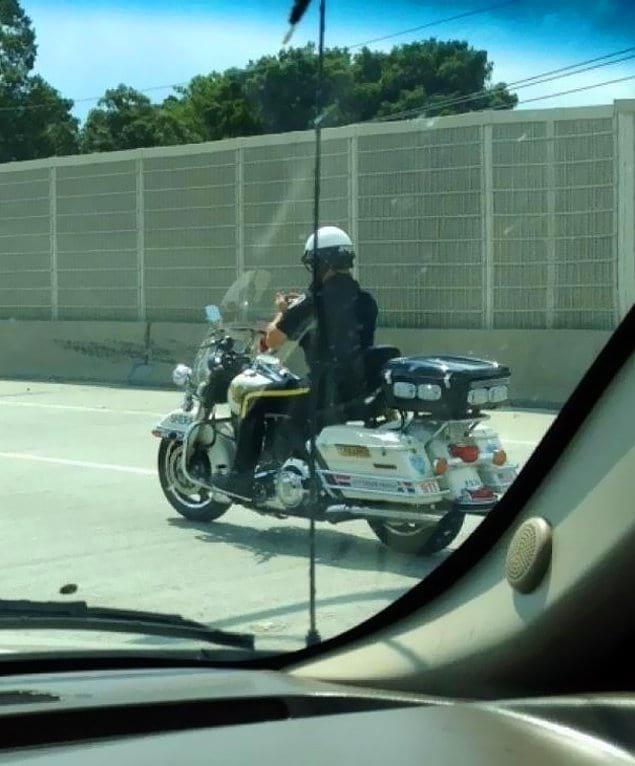 Полицейский, который пишет смс во время вождения мотоцикла.
