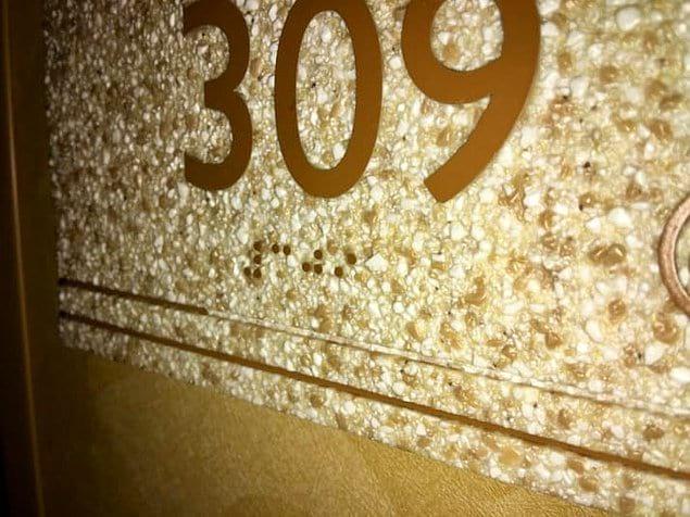 Снизу номер написан шрифтом Брайля, но поверхность стены-то неровная...