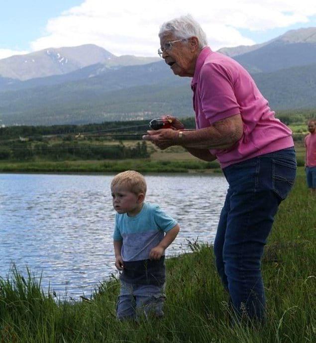 89-летняя бабушка и 3-летний внук держат свою первую рыбу, которую они поймали вместе.