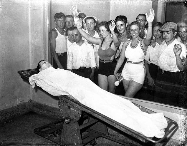 Граждане фотографируются с телом известного преступника, грабителя банков Джона Диллинджера, выставленном в морге для зрителей. США. 1934 год.
