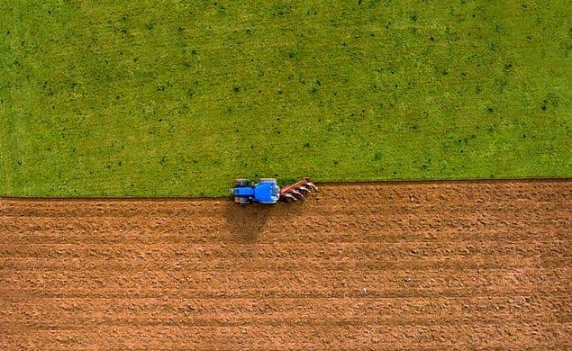 Поле, которое вспахивает трактор.