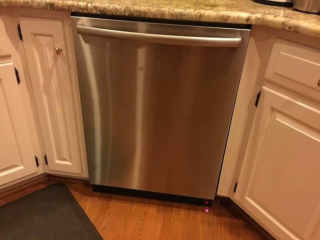 Посудомоечная машина проецирует на пол красный луч, который сообщает о том, что она работает.