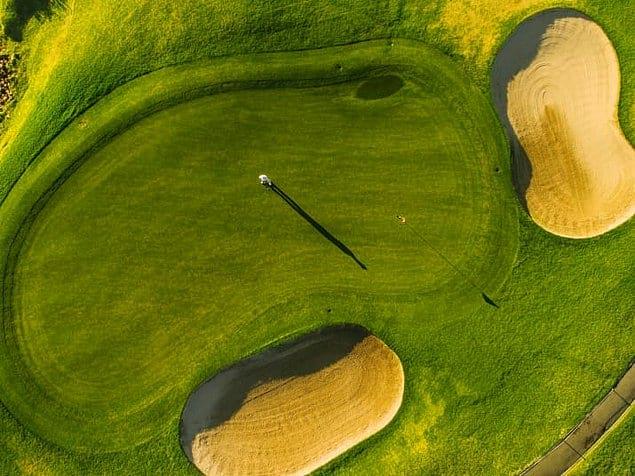 Радующее глаз ярко-зеленое поле для гольфа.