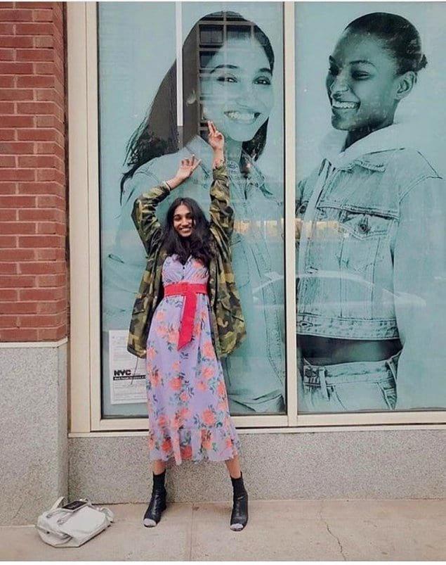Улыбающаяся модель на фоне своего первого плаката на Бродвее.