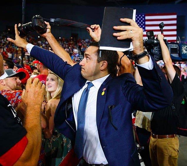 Член команды американского президента мешал работе фотожурналиста, когда тот пытался сфотографировать протестующих.