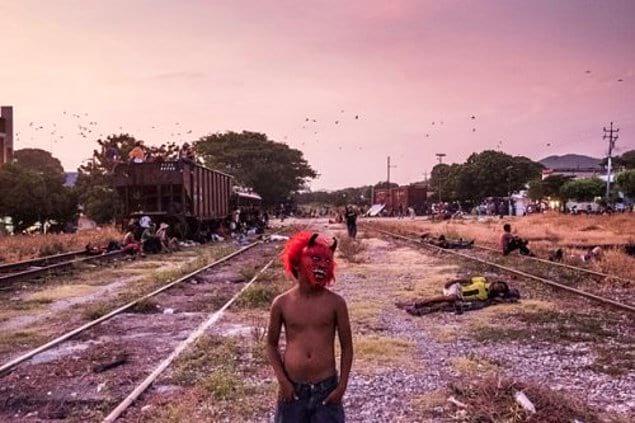 Мальчик из Гондураса играет, надев страшную маску.