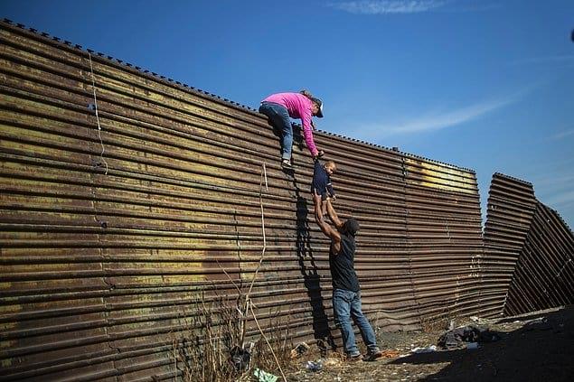 Мигранты из Центральной Америки перелезают через ограждение на границе между Мексикой и США.